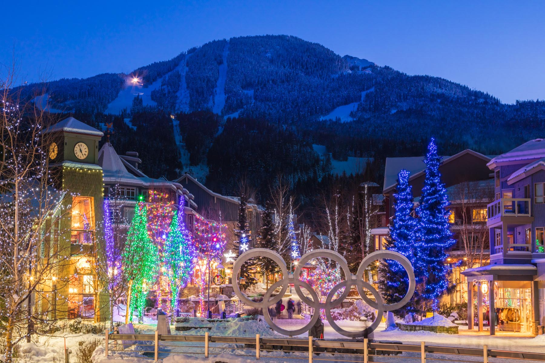 view of whistler mountain with whistler village lit with christmas fairy lights with the brewhouse pub